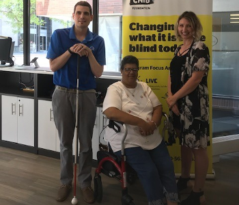 Ryan Hooey poses for a photo at the London Hub with Kristeen Elliott, a Deafblind community member and DBCS Ambassador, and Christine, an Intervenor.