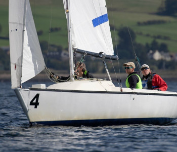 Joshua Cook and two other people sit in a sail boat on the water. They are at the World Blind Sailing Championships in Scotland.