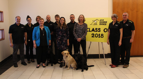 "CNIB Guide Dogs graduating class with training staff. A yellow sign in the background reads ""Class of 2018"""