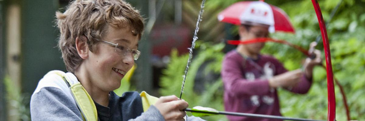 Boy with sight loss drawing a bow in archery