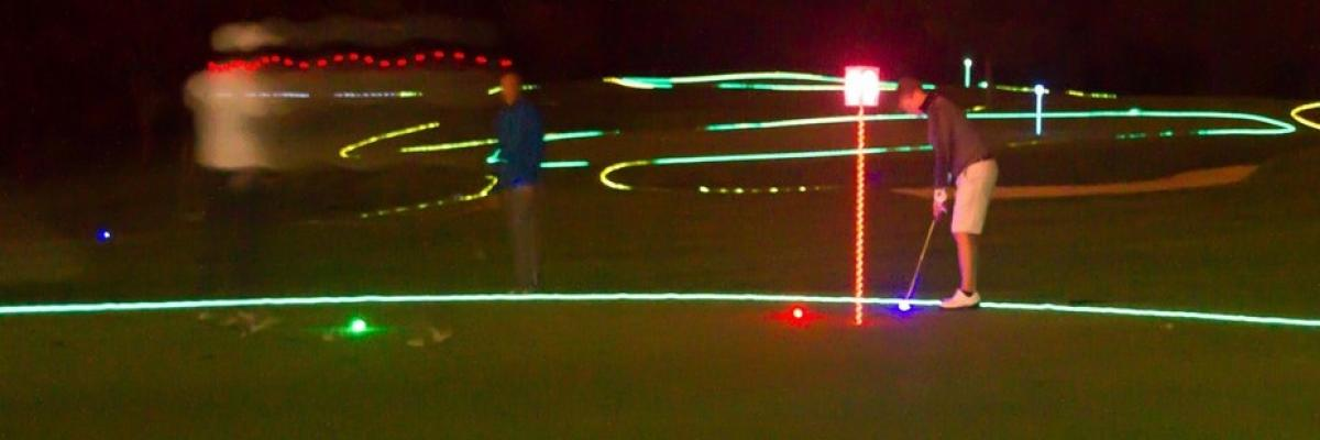 Golfers putting with golf course lit up