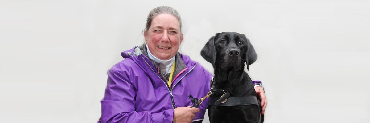 A woman in a purple jacket and her black Lab/Golden Retriever cross guide dog.