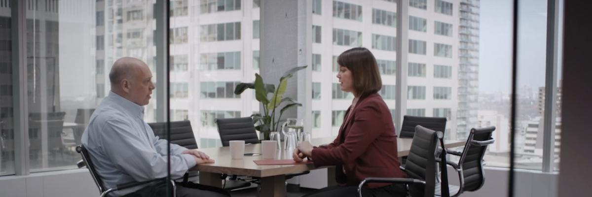 A man and a woman talking around a table during a job interview