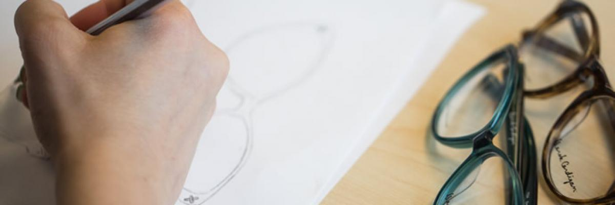 Photo of a person's hand, sketching on a white piece of paper with two pairs of glasses on the right.
