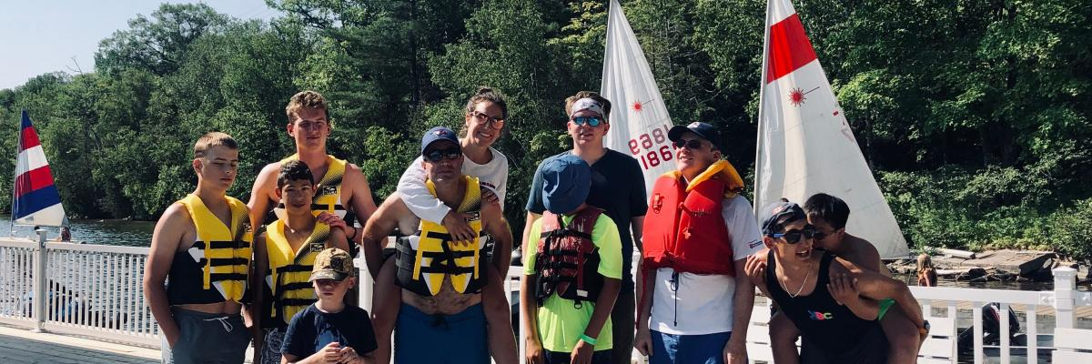 A group of people standing on the dock in shorts and life jackets. They are smiling and in some cases piggy-backing others.