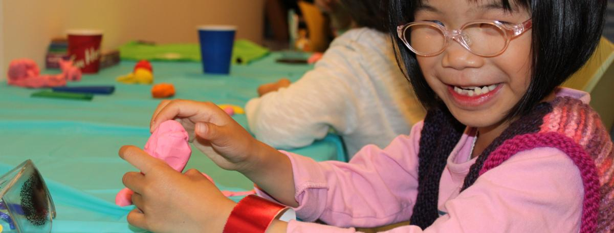 A young girl sits at a table creating a clay sculpture.