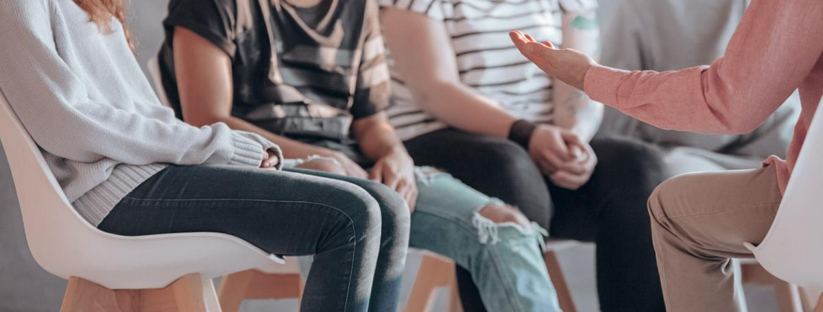 A group of five people sit in a circle and engage in lively conversation.