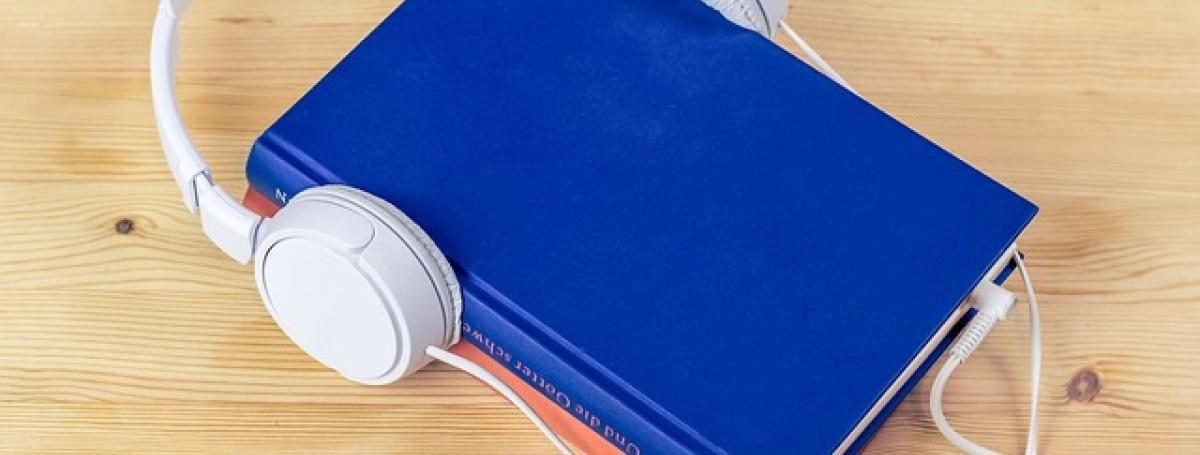 a blue book with headphones resting on top.