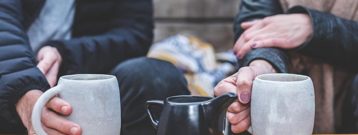 photo of two people seated at a table holding coffee mugs.