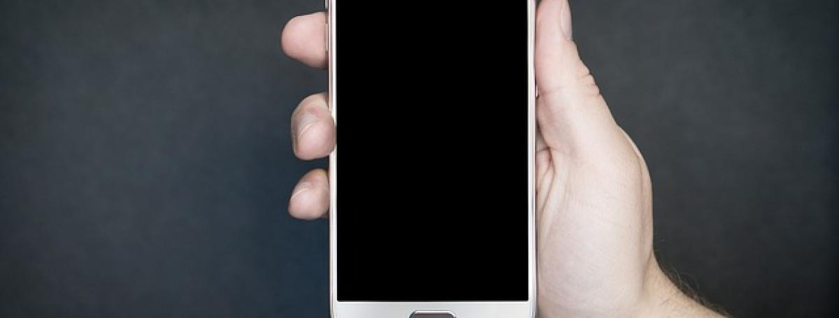 A hand holding an Android smartphone against a black background.