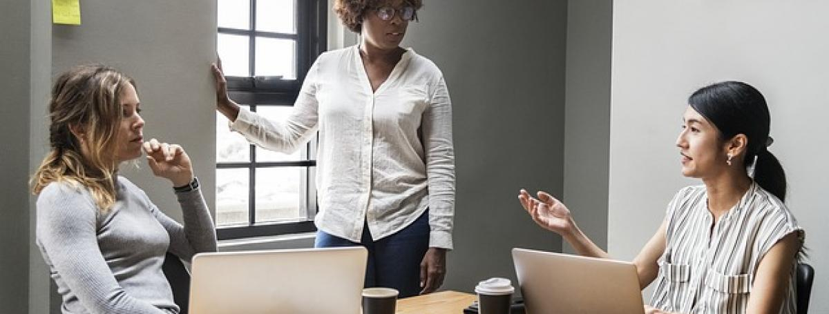 Three women in a meeting. Two women are sitting at a table in front of a laptop. Another woman stands near a window. They are engaging in a serious conversation.