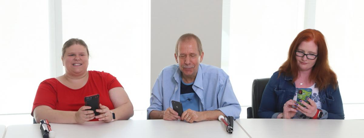 Three people sit with iPhones in hand and white canes sitting on the table in front of them