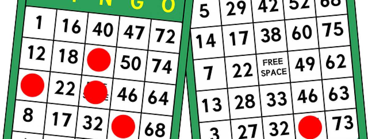An illustration of two bingo cards and red, circular, chips marking the card.