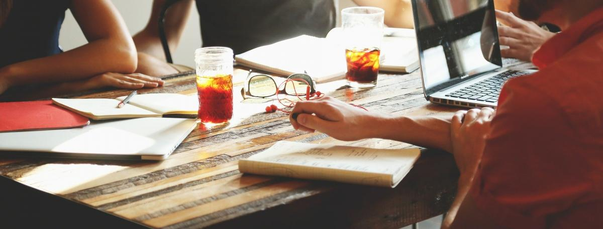 an extreme close up of 4 people sitting at a wooden table.  A laptop, paper, pens, glasses, notebooks are infront of them