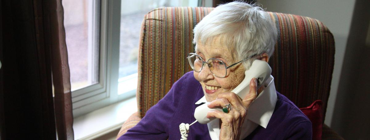 A woman, sitting in a recliner, is talking on a white phone.