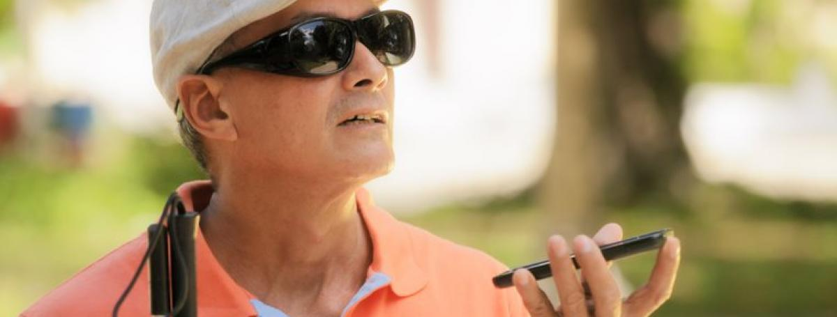 A man wearing sunglasses and a hat holds an iPhone in his left hand. A white cane sits in his right hand.