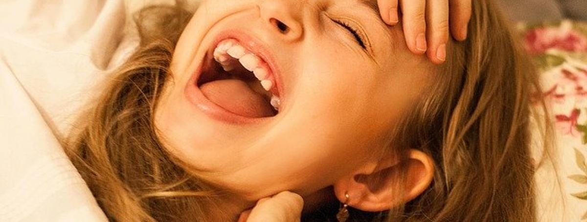 A young girl breaks out into a fit of laughter.