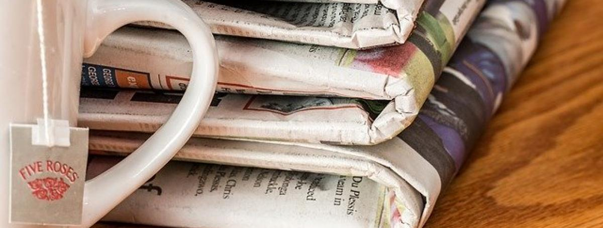 Three folded newspapers sits on a table next to a cup of tea.