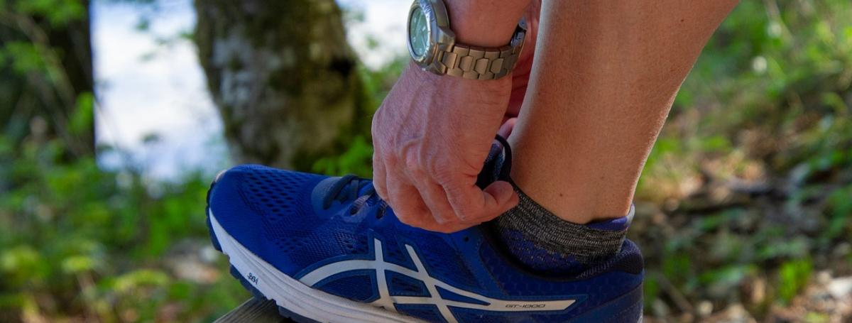 A person laces up a running shoe.