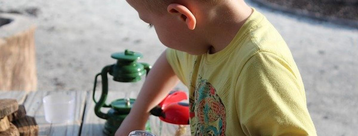A young boy holds a magnifying glass and plays at a table.