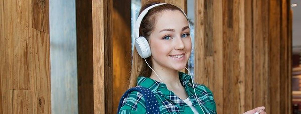 A young female student wears a backpack and headphones. The headphones are connected to her iPhone.