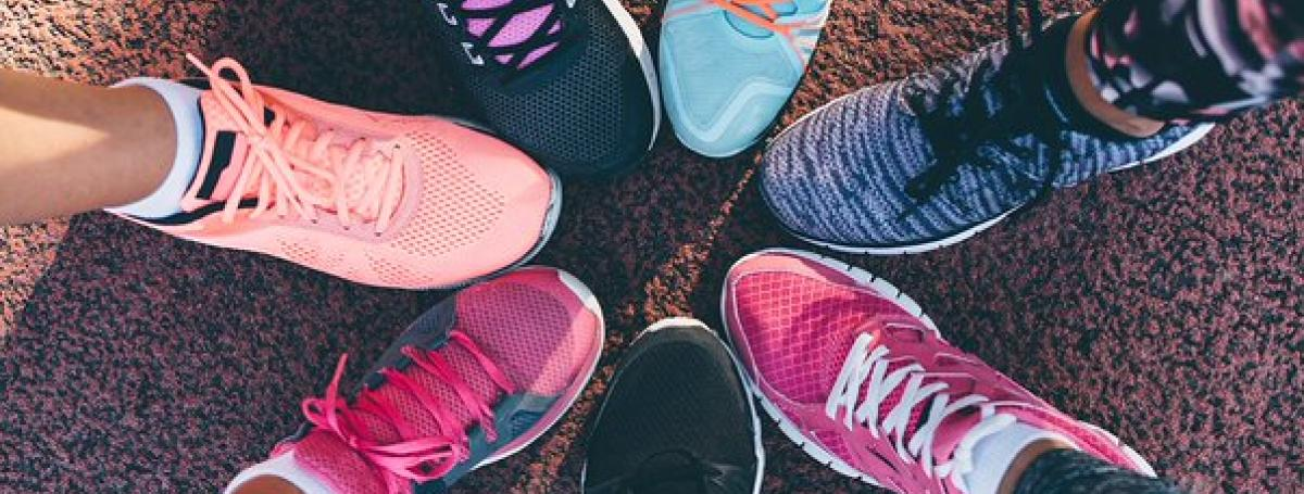 Six colourful running shoes stacked side-by-side in a circle.