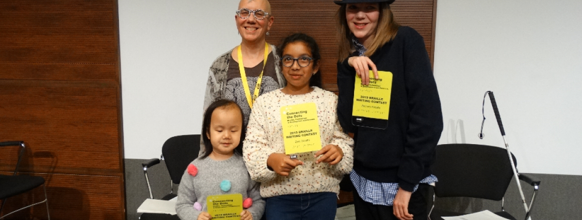 Winners from the 2019 Braille Creative Writing Contest Kelsey, Zara and Zachary pose for a photo with Karen Brophey. They are holding their awards!