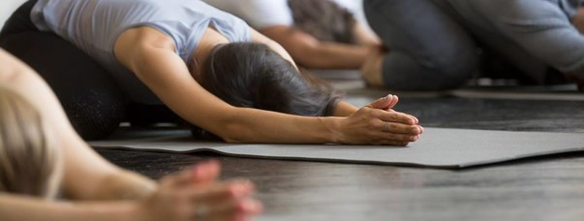 A yoga class. Three people kneel in a yoga position on their yoga mats.