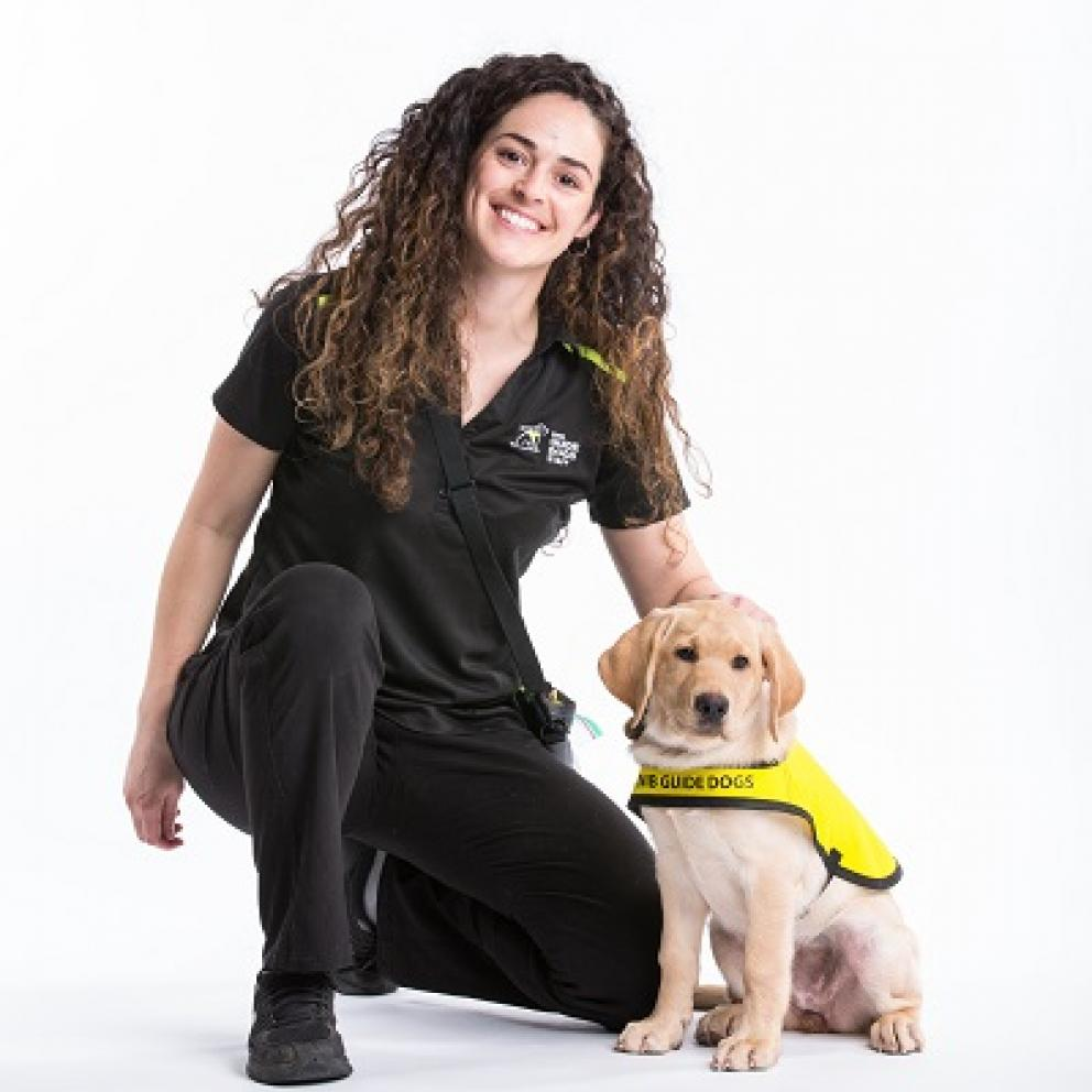 A CNIB Guide Dog puppy in training with her smiling handler