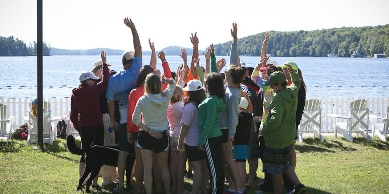 A group of  young campers huddle in a circle. Arms are raised in the air.