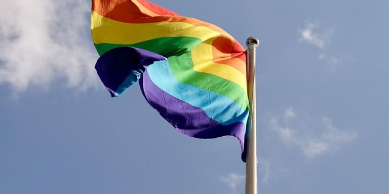 A colourful Pride flag waves in the wind on a flag post.