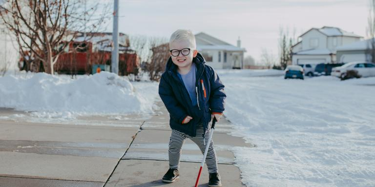 Little boy on a sidewalk with snow around him, holding his white cane like a hockey stick. He's smiling.