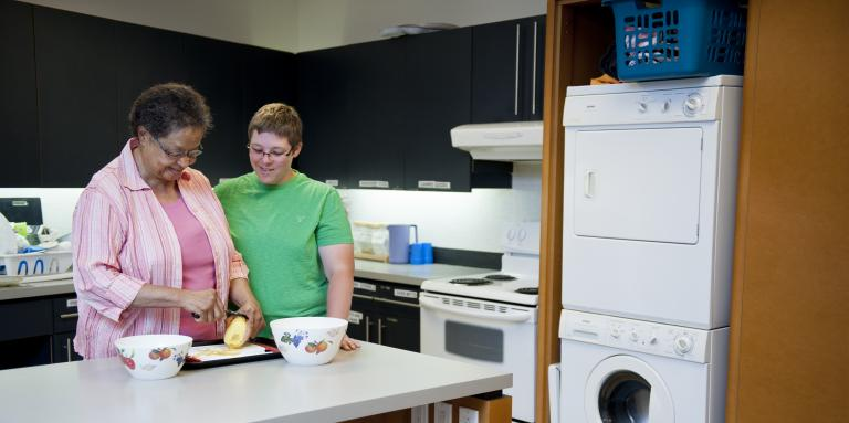 Two women are standing in front of a counter with a potato, cutting board and two bowls. The woman on the left in pink is peeling the potato, while the woman on the right, wearing green, if overseeing.