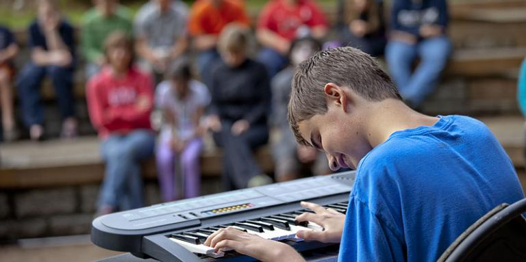 Teenage boy with sight loss playing keyboard for audience at talent show