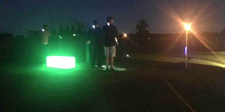 Golfers standing on the green with lights around them