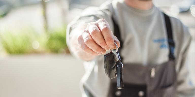 Photo of person holding out car keys