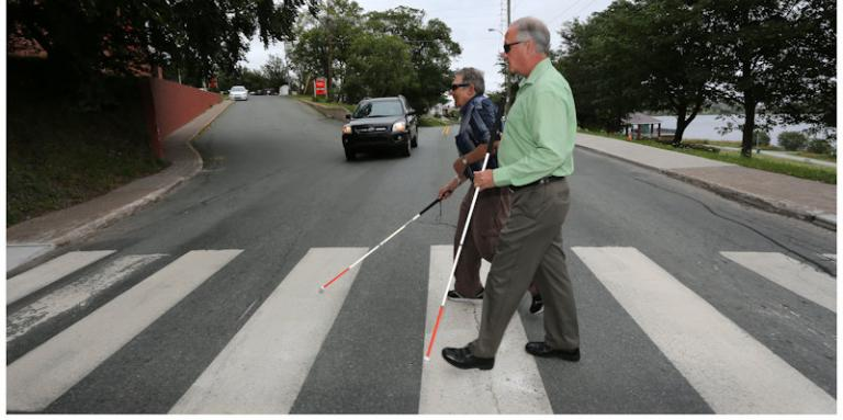 Men with canes crossing at a cross walk.