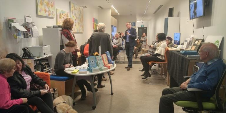 Photo of a Book Launch event with Terry Fallis speaking with group of CNIB participants.