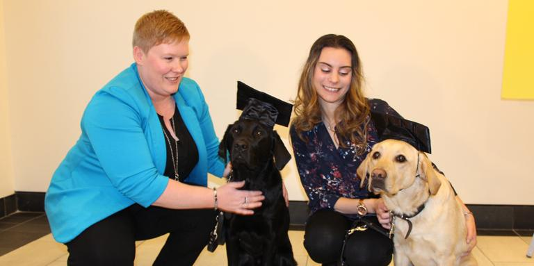 Ashley and Danika with two Lab/Golden Retriever crosses (one black and one yellow) wearing graduation caps.
