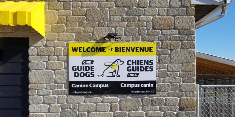 "A photo of the welcome sign placed on the exterior of the Canine Campus. It reads: ""Welcome & Bienvenue"" with the CNIB Guide Dogs logo in the middle of the sign."