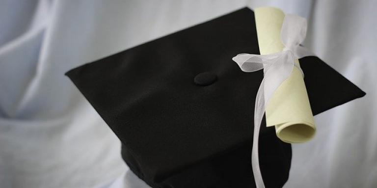 A white diploma scroll sits wrapped in a bow on top of a black graduation cap.