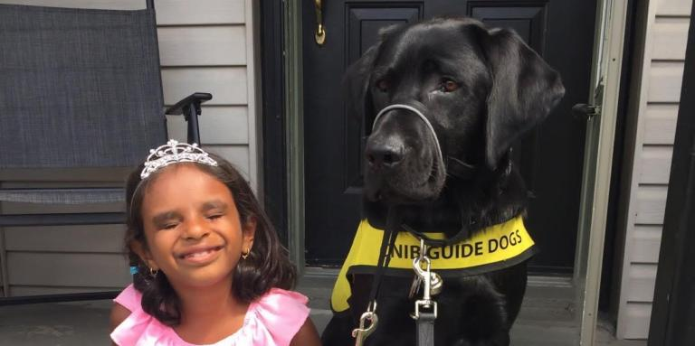 A young girl radiates joy and sits on her front porch stoop alongside her CNIB buddy dog.
