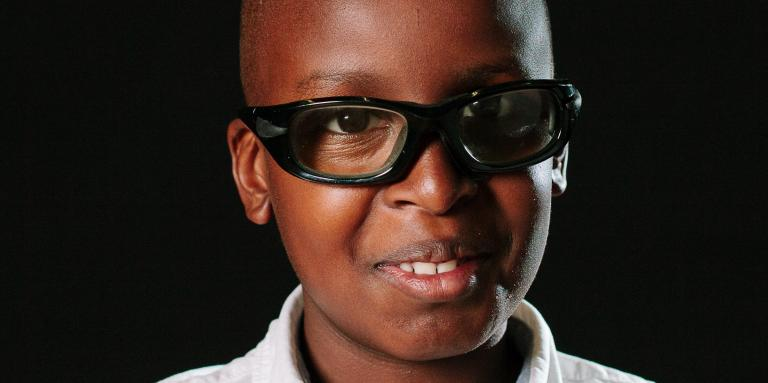 A young boy smiles for a school photo. He is wearing glasses and a polo shirt.