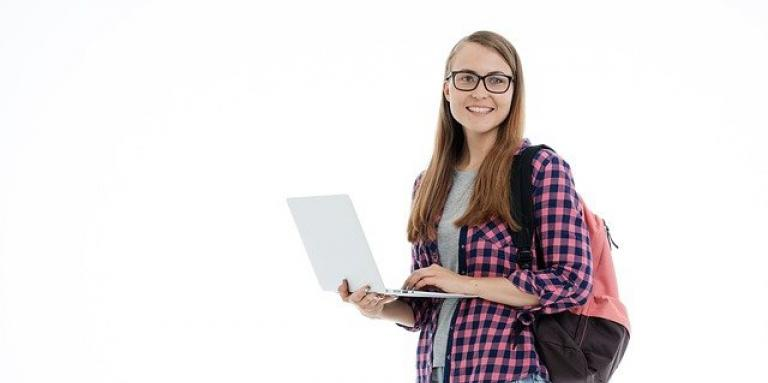 A college student stands while holding/typing on her laptop with her left hand. She is wearing a backpack