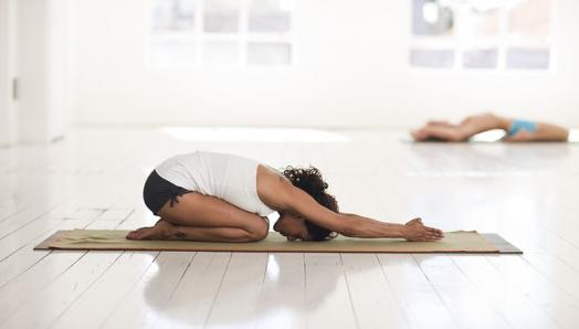 A woman kneels on a yoga mat and stretches in a downward dog pose.