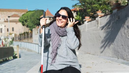 A young woman sits alone outdoors. In her left hand, she is holding her smartphone up to her ear. In her right hand, she holds her white cane