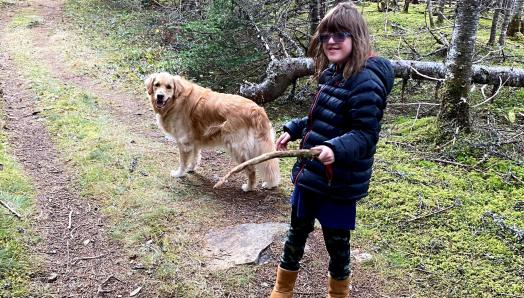 Rhea and her CNIB Buddy Dog Ivy, a two-year-old golden retriever, walking along a trail in the woods. Rhea is holding a stick and they are both looking back at the camera, smiling.